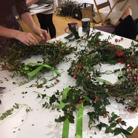 participant at a worktable creating a wreath