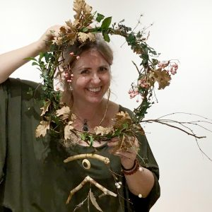 smiling woman holding up and looking through her completed handmade wreath