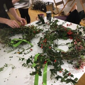 participant at a worktable piecing together a wreath